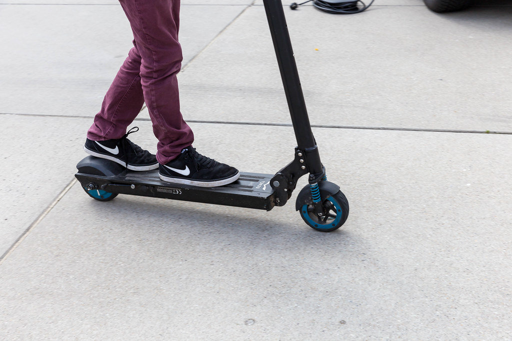 Boy in Nike shoes tries out the innovative Egret One electroscooter at the E-Cologne trade show