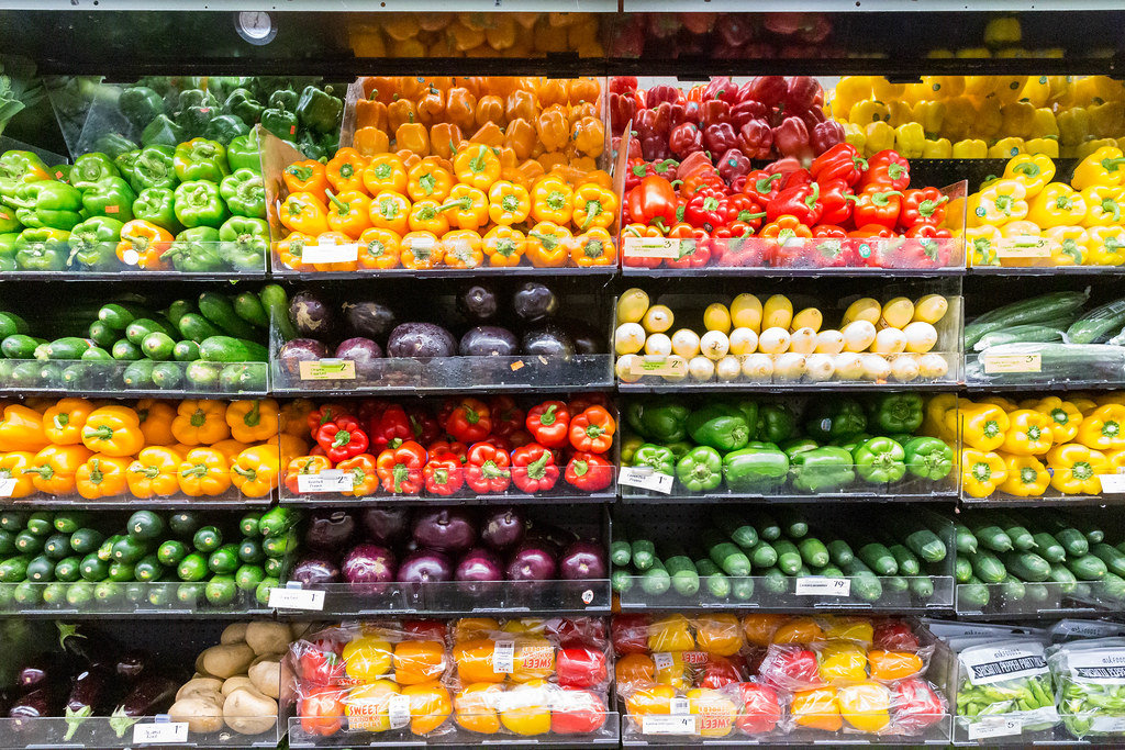 Colorful supermarket shelf with different vegetables like eggplants, cucumbers, and all sorts of bell pepper