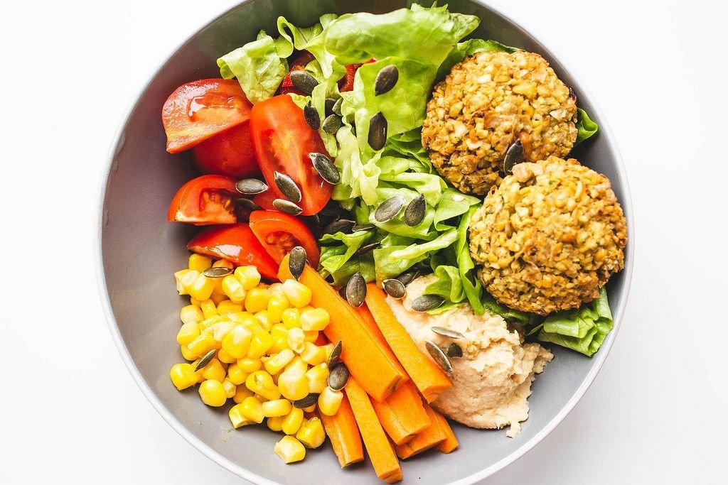 Vegetarische Ernährung – Falafel mit Humus, Salat, Gemüse und Sonnenblumenkernen