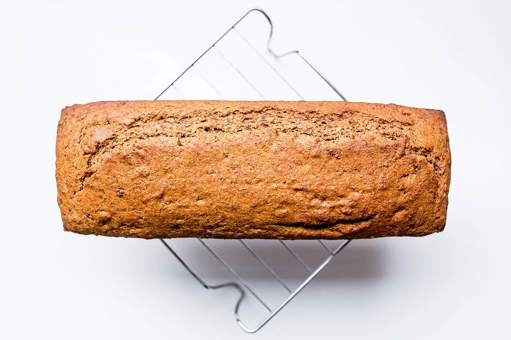 Top view of banana bread loaf on cooling rack on white background