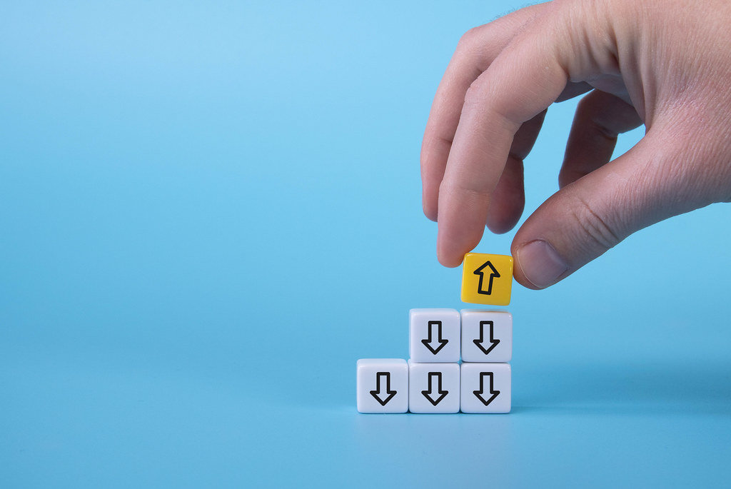 White cubes with down arrows and one yellow cube with arrow up