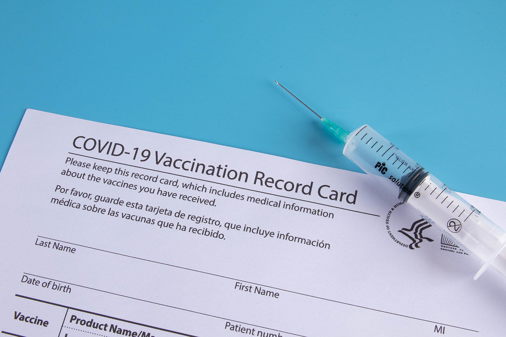 Syringe and vaccination record card on blue background