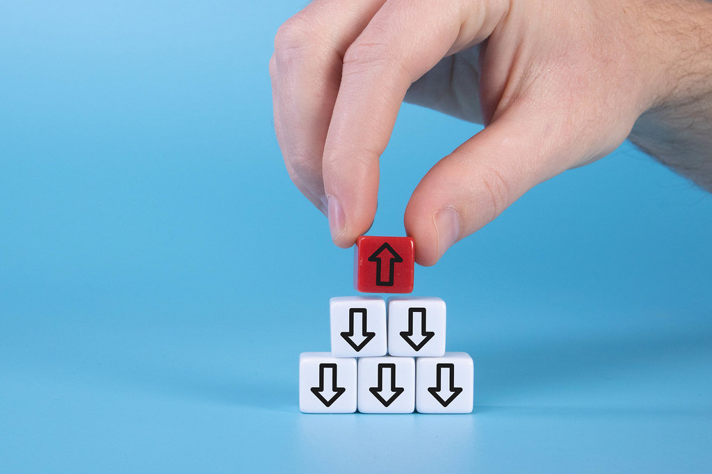 hand with white cubes with down arrows and one red cube with arrow up