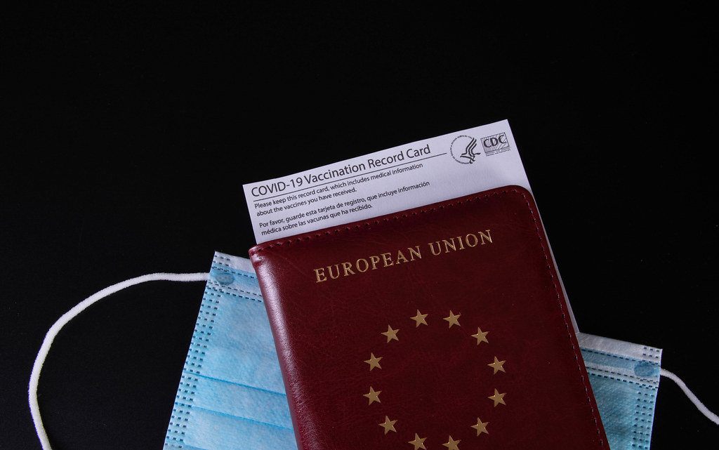 Passport, medical face mask and Vaccination record card on black background
