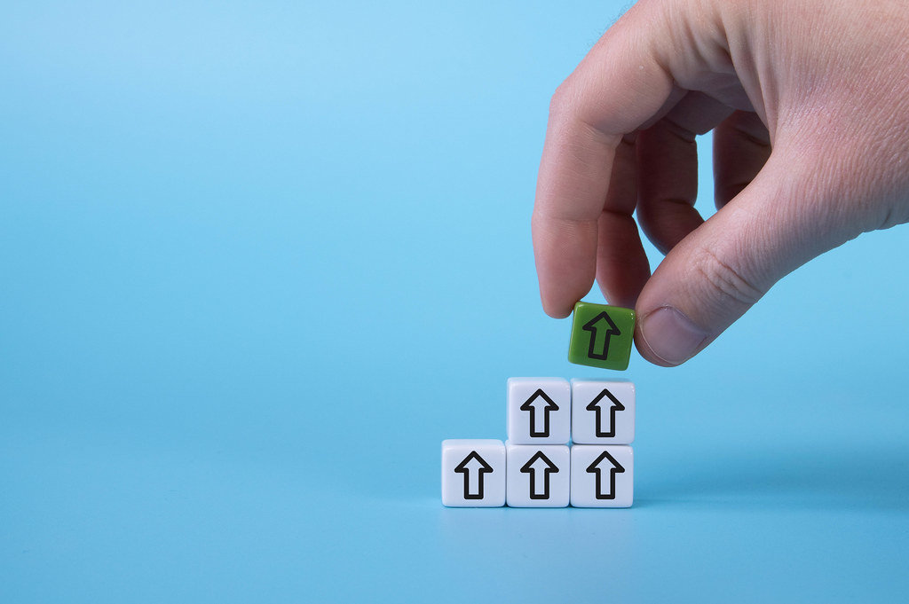 White cubes with down arrows and one green cube with arrow up