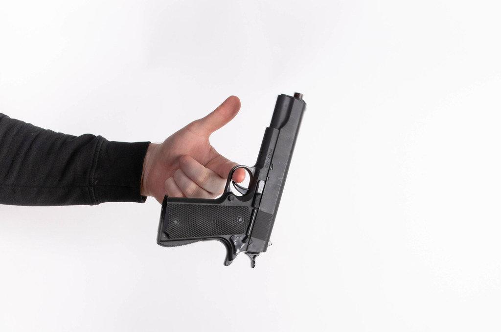 Mans hand holding gun, isolated on white