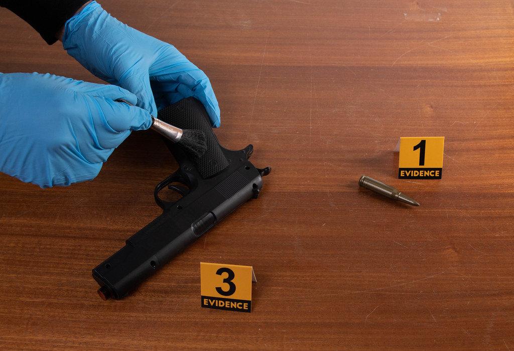 Detective in gloves investigating gun at crime scene