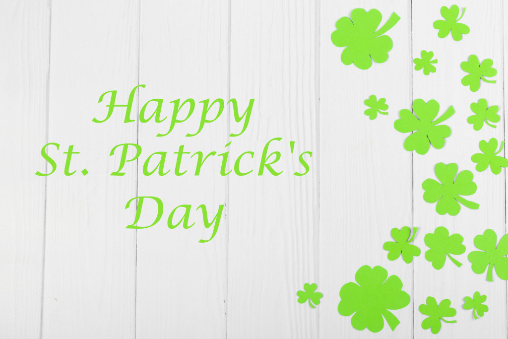 Happy saint patricks day greeting card with traditional symbol-shamrock and four-leafed clover on wooden background