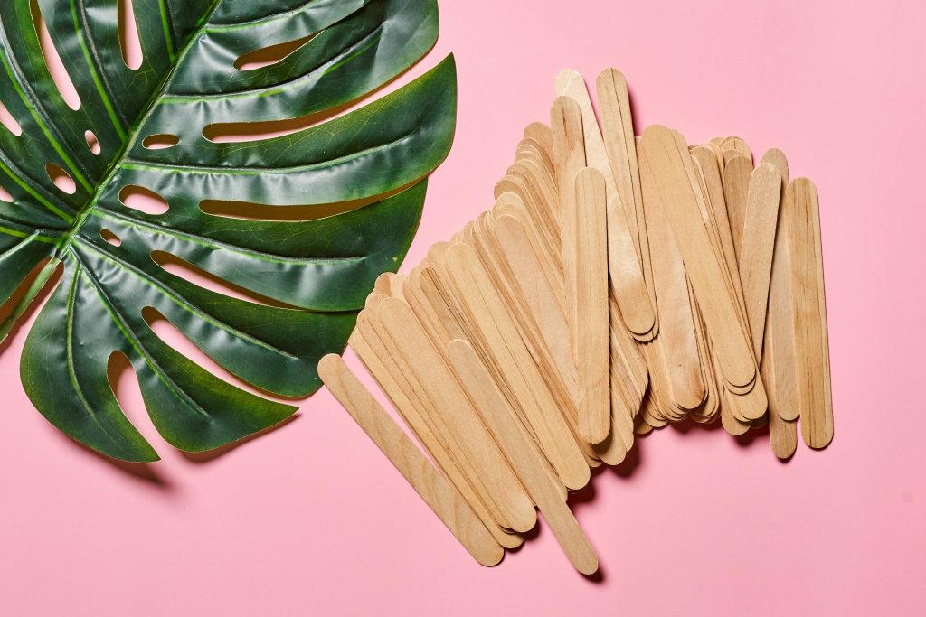 Wooden waxing spatula sticks and big palm leaf