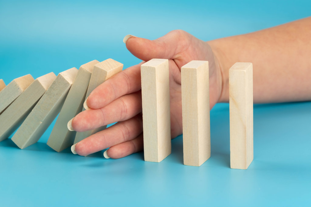 Risk and strategy in business, close up of hand stopping wooden block from falling in the line of domino