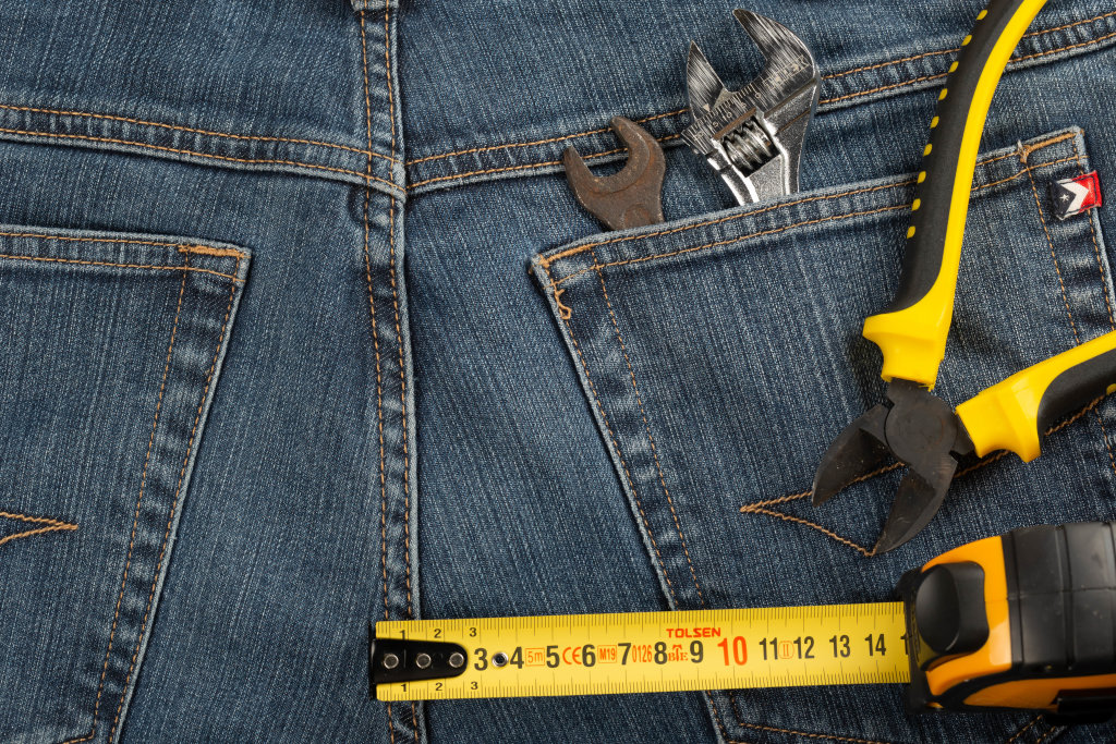 Measuring tape, wire cutters and wrenches on jeans background