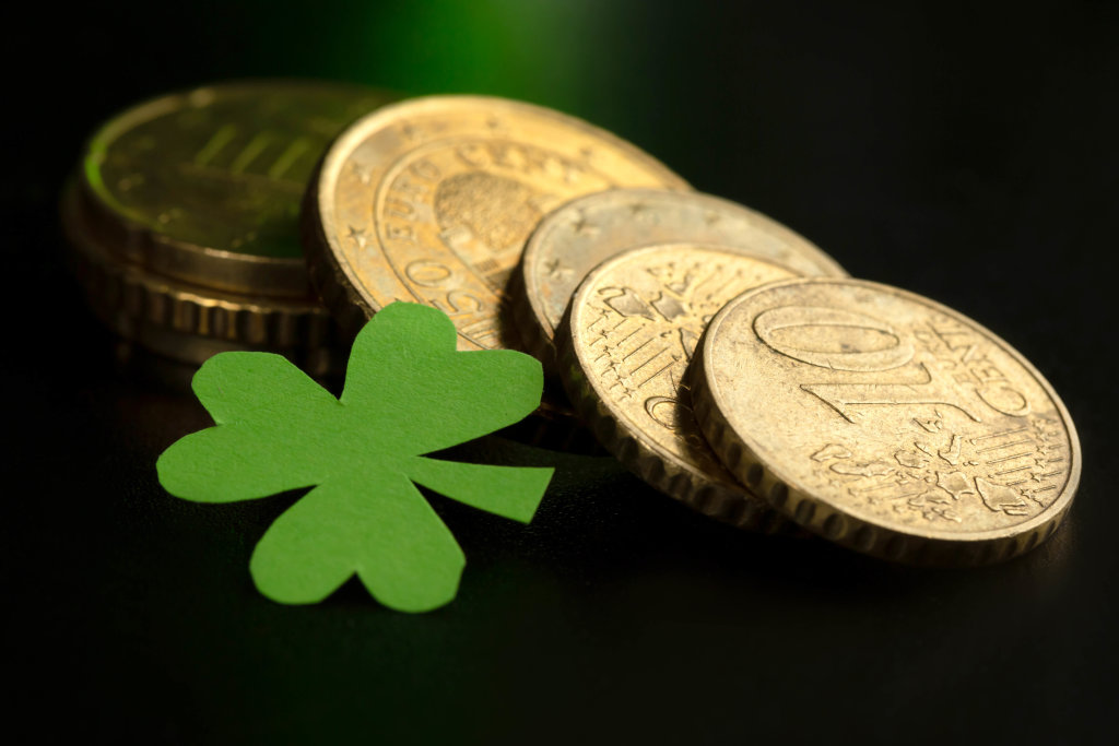 Coins and shamrock leaf on dark background, close up