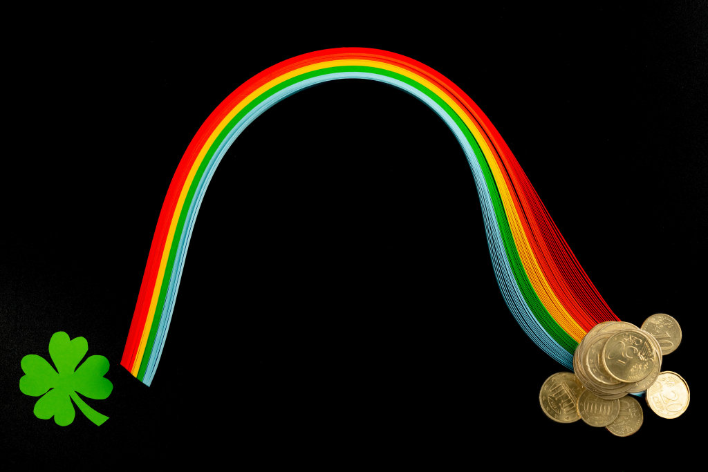 Rainbow from multi-colored paper with coins and paper clover leaf on a black background