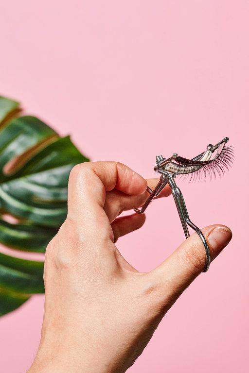 Close-up shot of beauty stylist holding eyelash curler over pink background