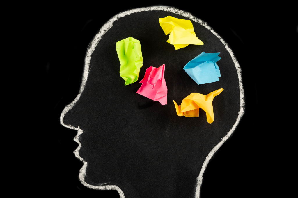 Concepts for generating ideas and solutions, multicolored papers in a drawn head silhouette