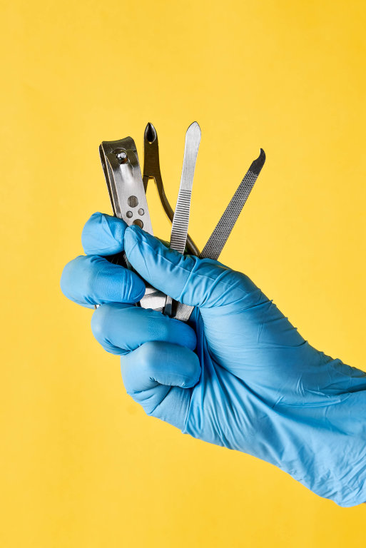 A persons hand in medical gloves holding manicure and pedicure tools