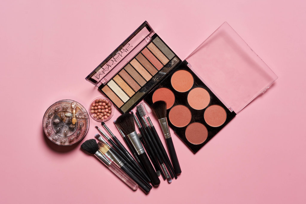 Makeup professional cosmetics on pink background.