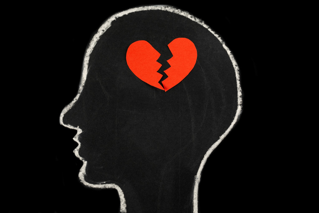 Cut halves of a heart in a silhouette of a human head, the concept of loss, stop loving
