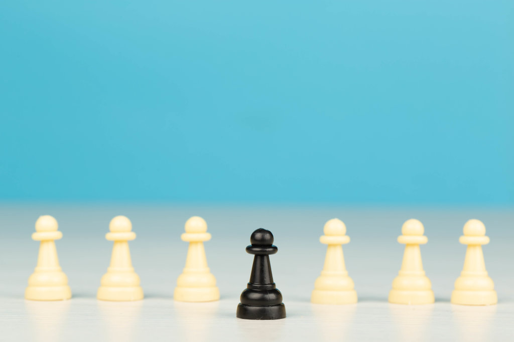 One black pawn in front and many white ones behind, business concept