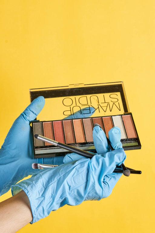 Make-up artist hands hold blush and brush
