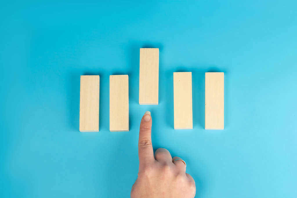 Choice concept, finger points to wooden block in front, blue background, top view