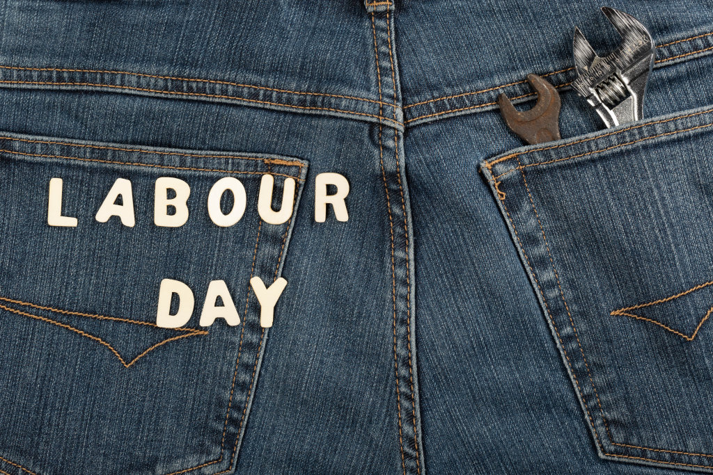 Labor day from wooden letters on denim with wrenches in pocket
