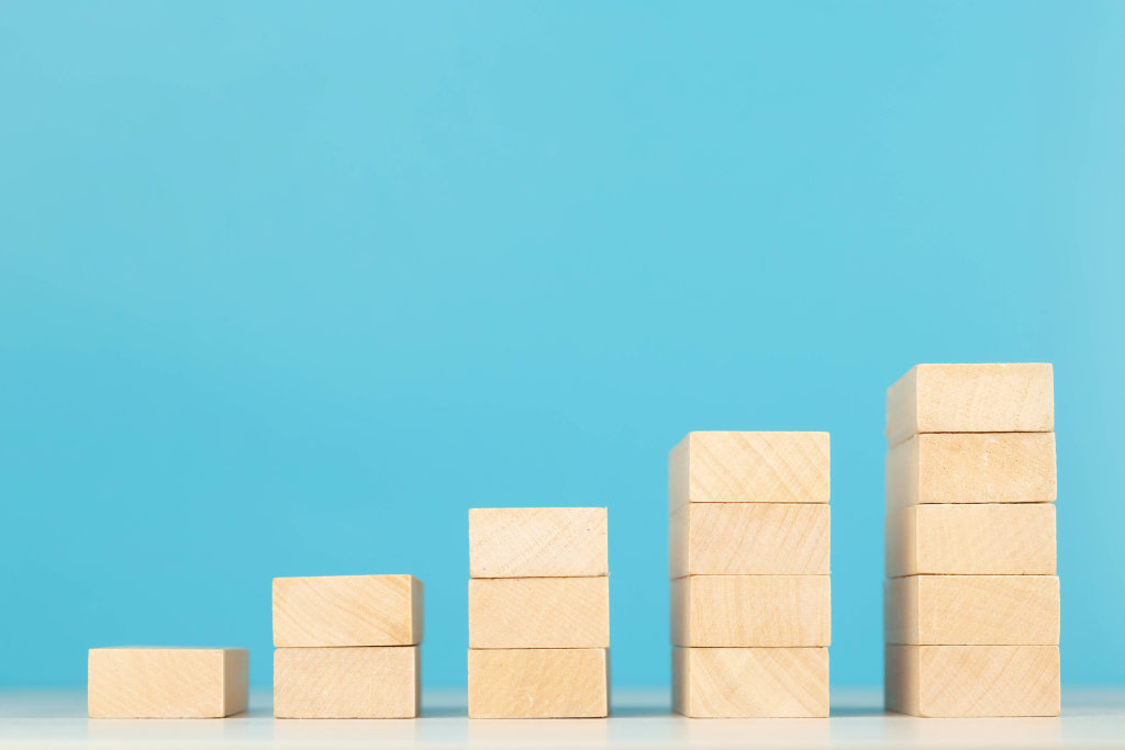Wooden blocks in shape of a ladder, business growth concept