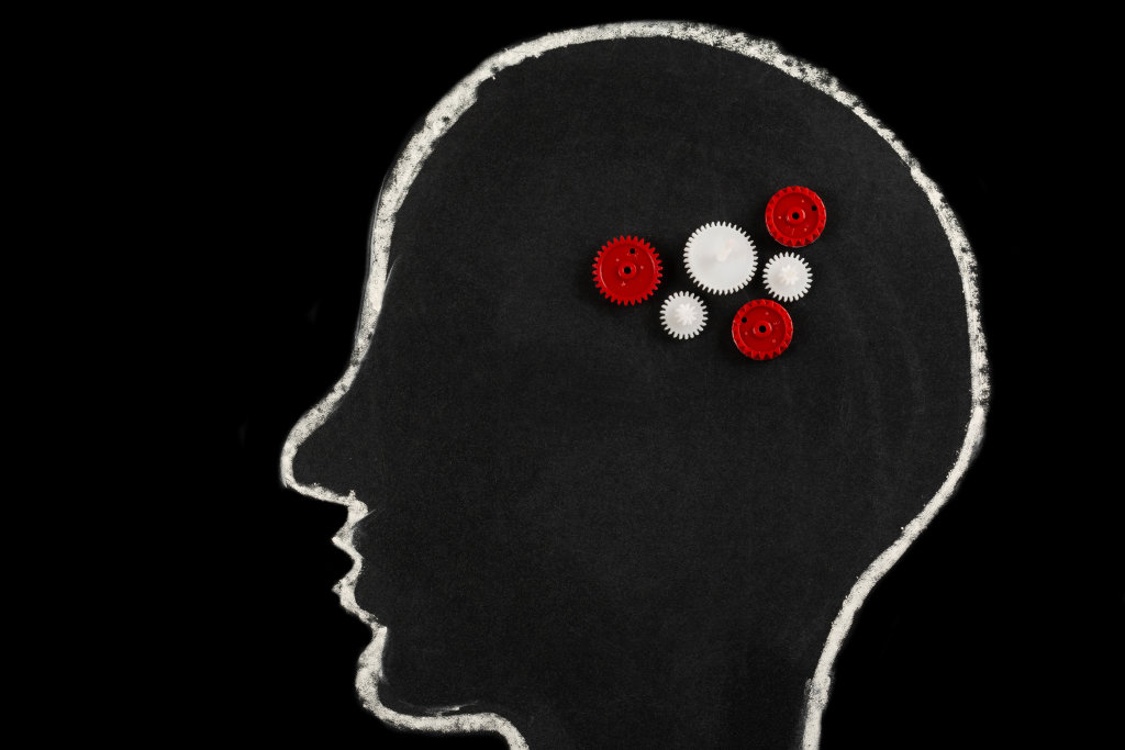 Chalk-drawn silhouette of a human head with gears on a black background, human brain concept