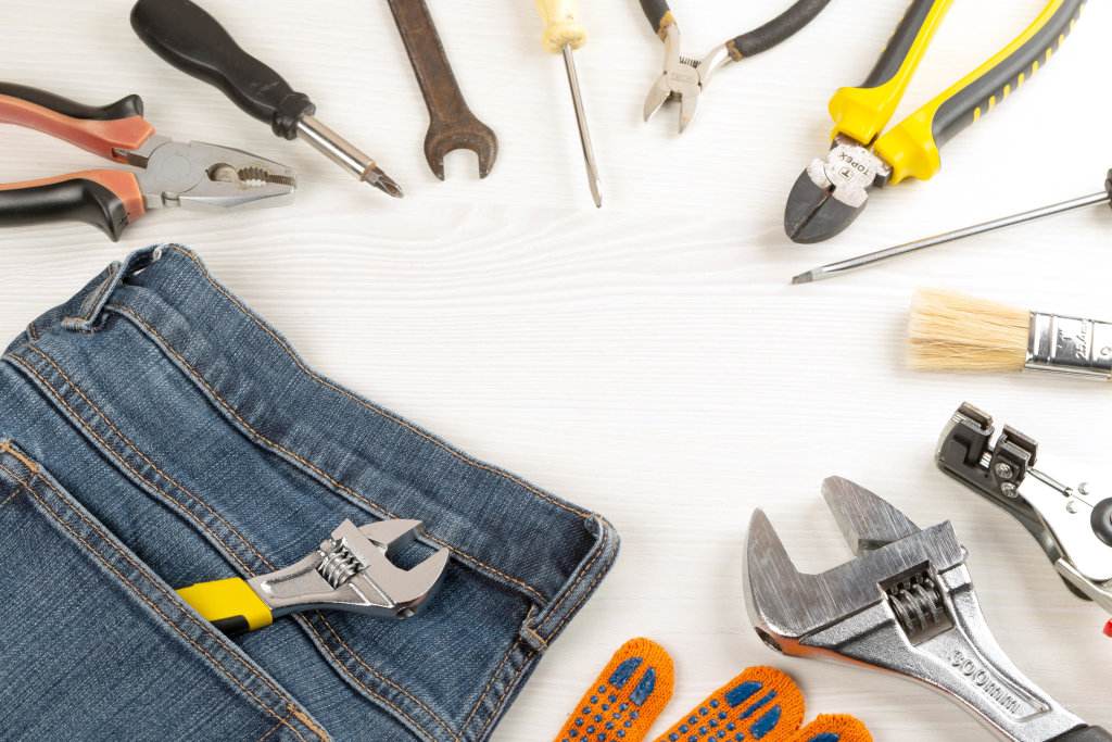 Top view, frame from work tools, glove and jeans on wooden background