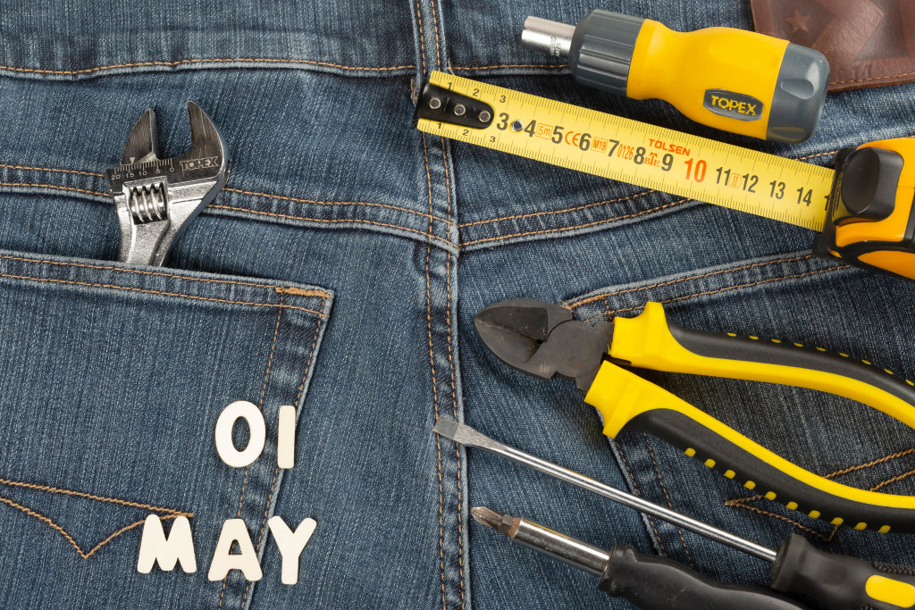 The concept of labor day-the first of may made of wooden letters on the background of jeans with hand tools