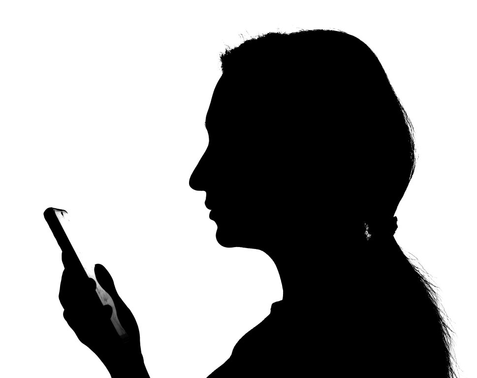 silhouette of a businesswoman using a smartphone