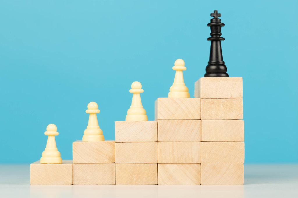Chess standing on a ladder of wooden building blocks with the king at the top