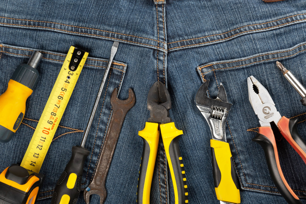 Set of working tools on jeans background, top view