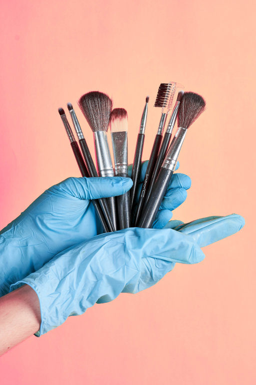 Set of make-up beauty brushes in beautician hands in gloves
