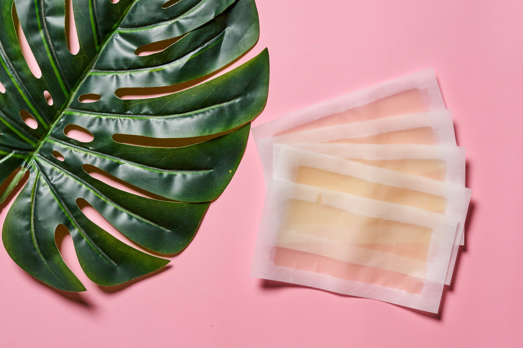 Wax strips with honey on bright pink background