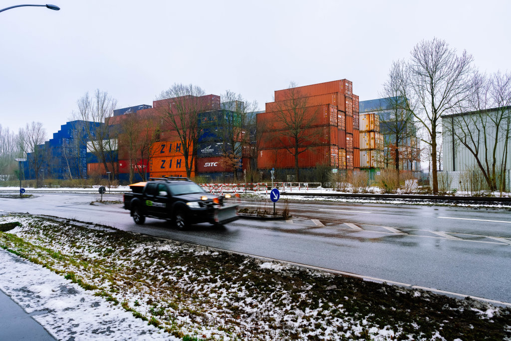 Winter service vehicle driving past the shipping containers storage in Hamburg's port
