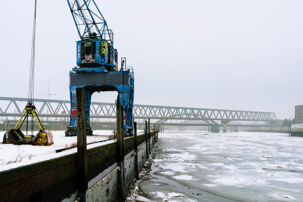 Blue abandoned port crane covered in Graffiti on the loading dock with frozen water below