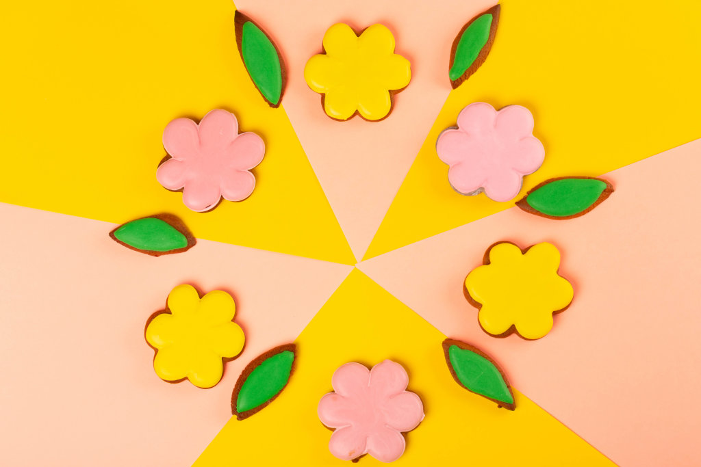 Gingerbread cookies - flowers with colored glaze on a pink and yellow background, top view