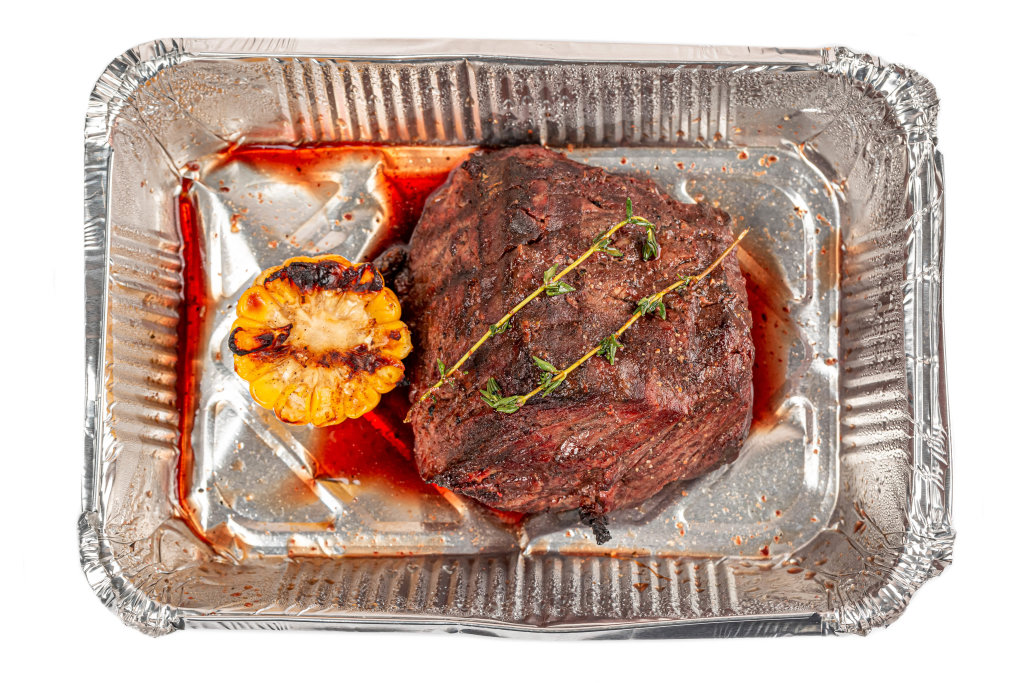 Fillet mignon with thyme sprig and grilled corn in a container, top view