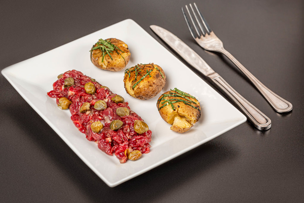 Fresh beef tartare with capers and potato on plate, dark background