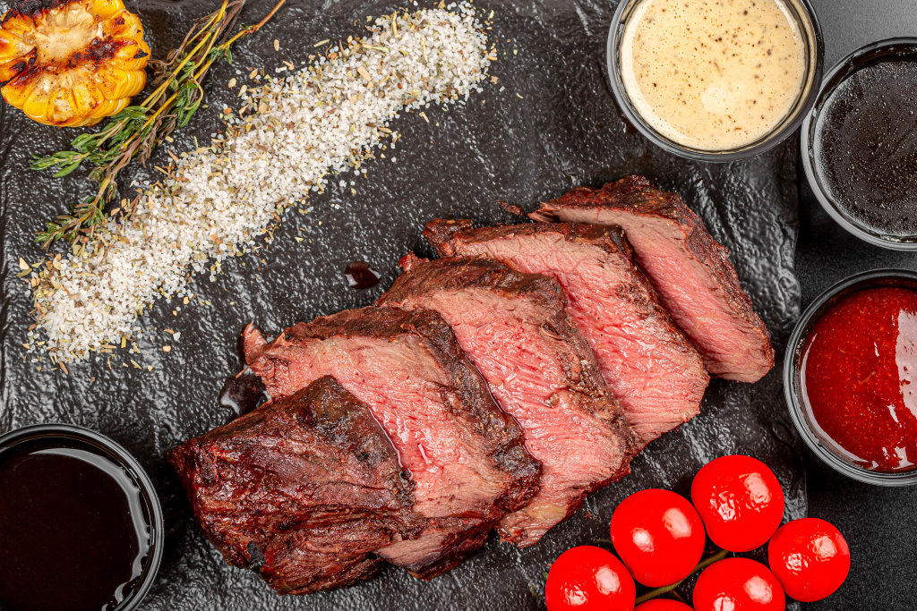 Grilled beef steak pieces on black background with spices and sauces