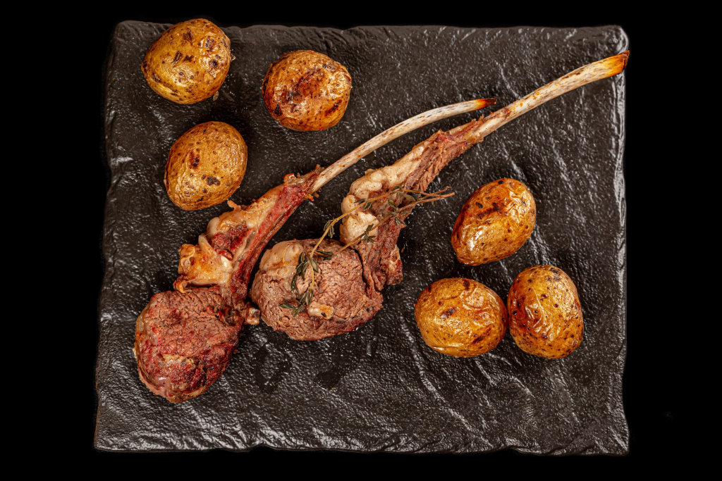 Top view, grilled lamb ribs and potatoes with thyme on dark background