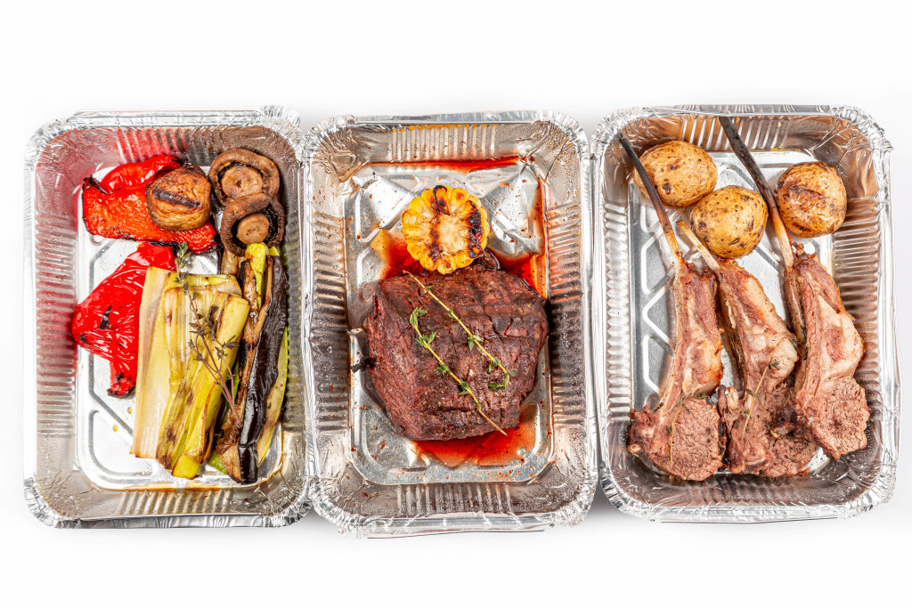 Grilled vegetables, filet mignon and lamb ribs in containers, top view