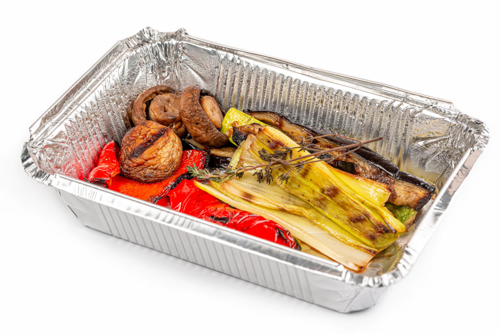 Grilled vegetables in a foil container on a white background
