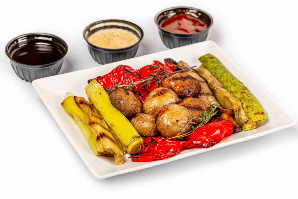 Grilled vegetables appetizer with sauces on white background