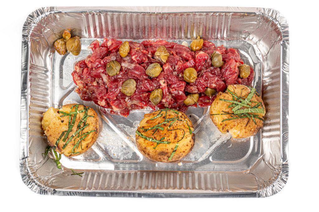 Beef tartare with potatoes and capers in a container, top view