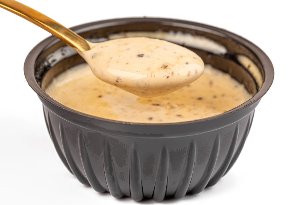 Garlic barbecue sauce in a spoon, close-up