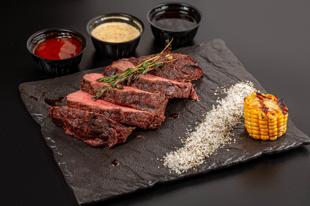 Sliced pieces of grilled beef with spices, thyme and sauces on a dark background