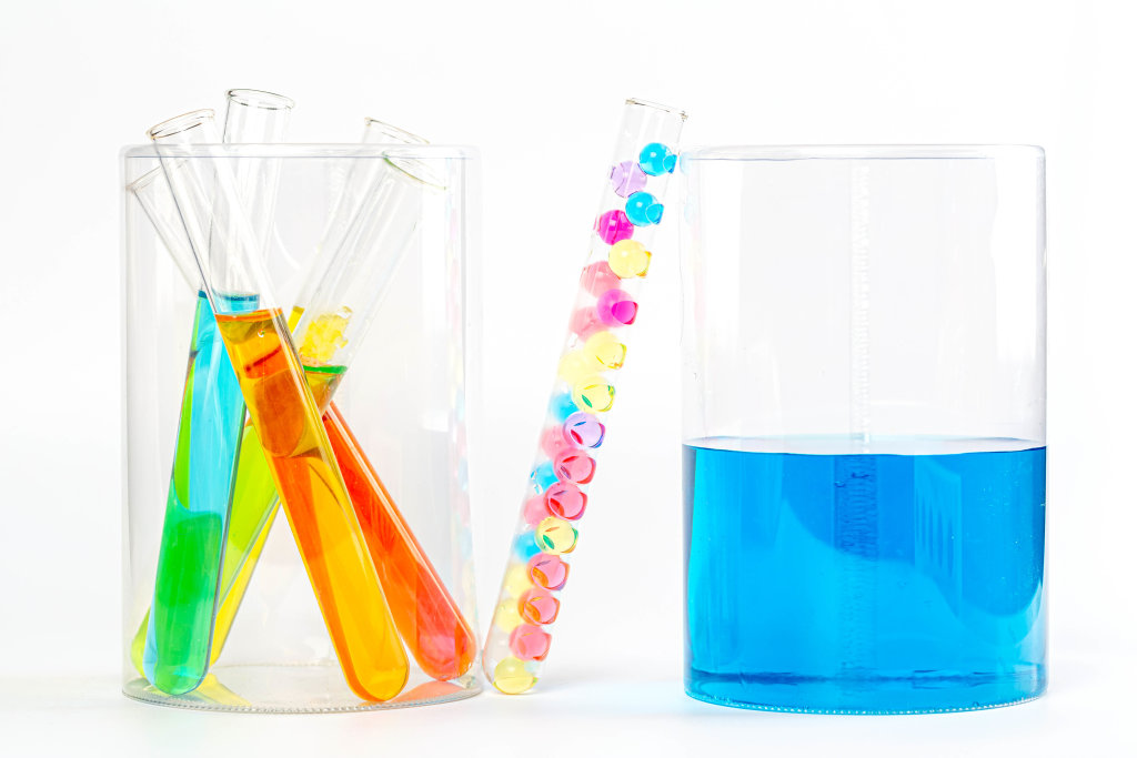 Test tubes in laboratory with colorful liquids and balls on white