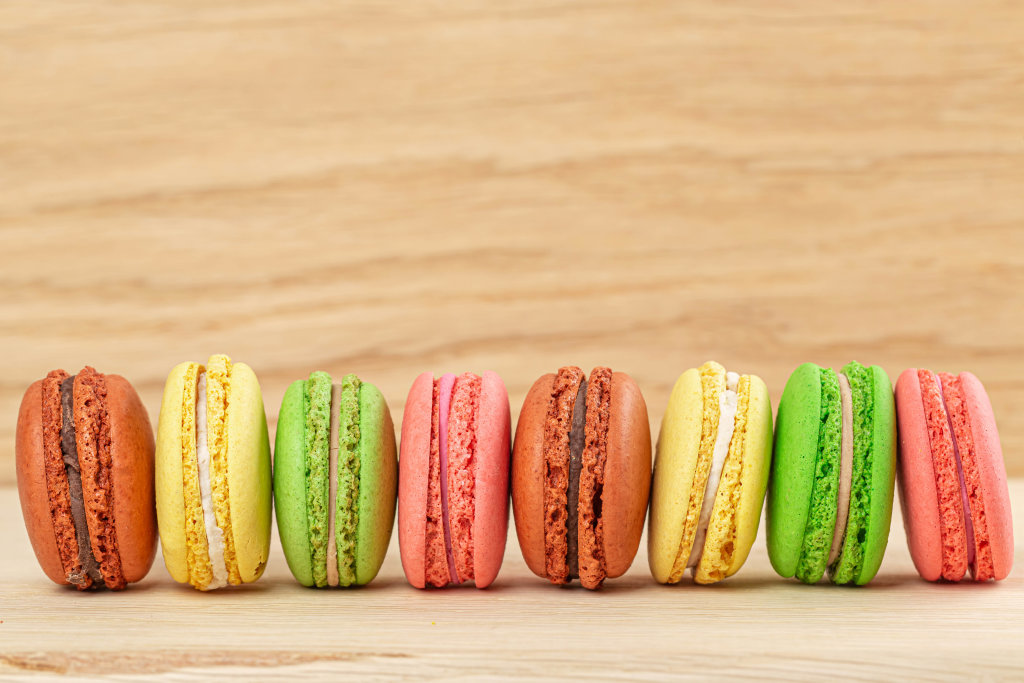 Traditional french colorful macaroons in a row on wooden background